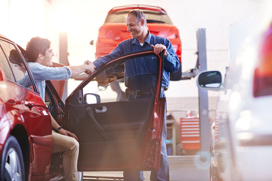Mechanic and customer in car handshaking in auto repair shop
