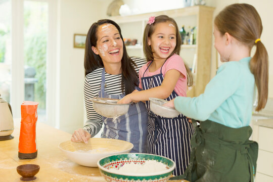Laughing mother and daughters baking with flour on faces in kitchen