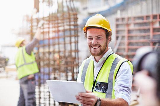 Portrait confident construction worker digital tablet at construction site