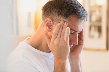 Man with headache rubbing temples