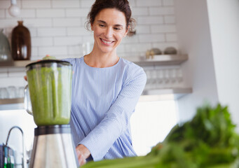 Smiling woman making healthy green smoothie in blender in kitchen