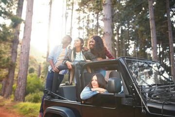 Young friends in jeep looking up at trees in woods, enjoying road trip