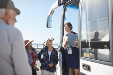 Tour guide talking to active senior tourists at doorway of tour bus Fotobehang