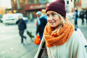 Young woman in stocking cap and scarf on urban street