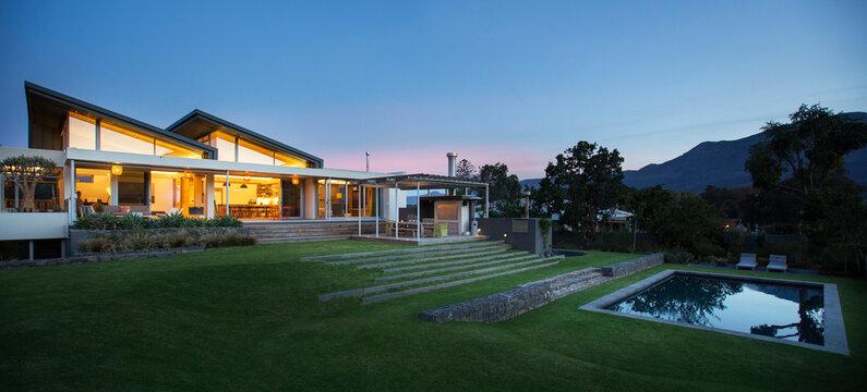 Illuminated modern house beyond yard and swimming pool at night