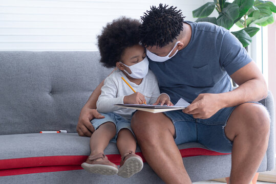 African father and son with protective masks on couch at home, protect infection from coronavirus covid-19 on table, the new normal social distancing concept