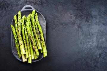 Traditioneller gegrillter grüner Spargel mit Kräuter als Draufsicht auf einem Modern Design Teller mit Textfreiraum rechts