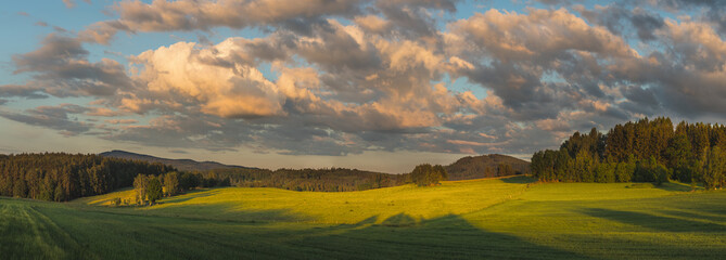 beautiful sunset landscape with meadows, trees, forests, in the background wooded hills and blue sky with clouds