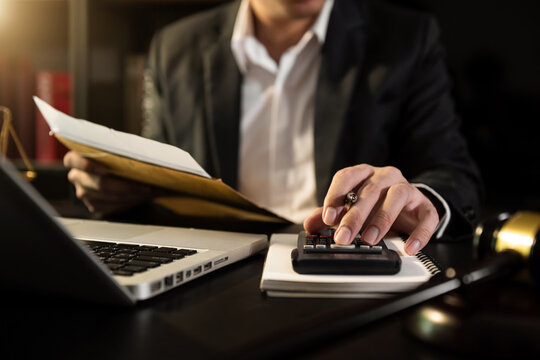 justice and law concept.businessman or lawyer or accountant working on accounts using a smart phone laptop digital tablet  calculator  and documents in dark office