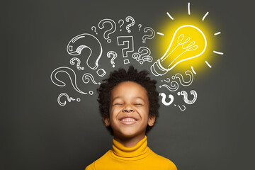 Happy black kid on black background with light bulb and question marks. Brainstorming and idea...