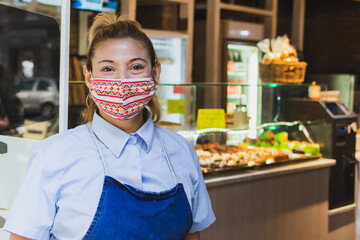 waitress with a face mask at the entrance of the cafeteria