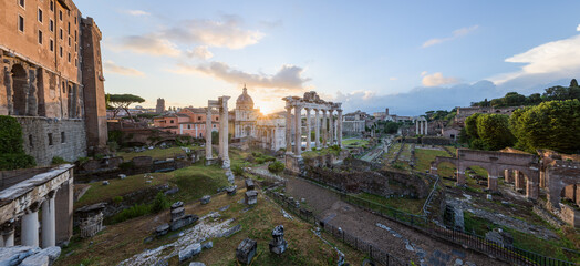 Cityscape of the Roman Forum ancient ruins with the Arch of Severus, temple of Saturn, temple of Vesta, Basilica of Maxentius, Arch of Titus and Colosseum at sunrise, in Rome, Latium, Italy