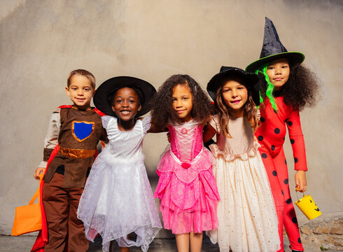Group of kids in Halloween costumes hug standing together and smiling looking at camera
