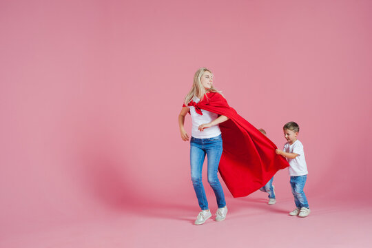 Mom is a superhero. Fun family, a young blond woman in a red Cape and her son,