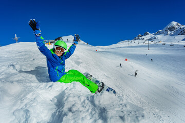 Little boy with snowboard sit on the snow view from side in mask, ski helmet lifting hands up