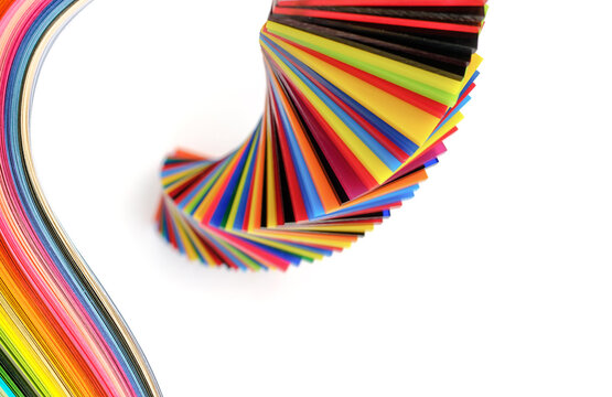 spiral Stack of different colours Cast Acrylic Sheet and rainbow strip paper on white background