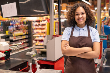 Young smiling shop assistant or cashier in workwear crossing arms by chest
