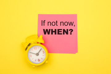 If Not Now When, text on a pink sticker with yellow alarm aside. Motivating and inspiring question.