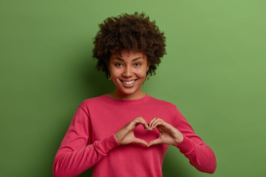 Shot of pretty African American woman expresses love, being in romantic mood, shows heart sign, confesses in truthful feelings, has sympathy, dressed in rosy jumper, poses against green studio wall