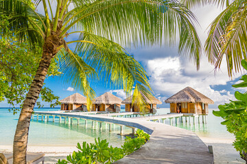 Luxury water villas bungalows in the Maldives islands, sunny hot weather as blue sky and white clouds. Idyllic and exotic scenery, jetty over blue lagoon. Summer holiday and beach vacation concept