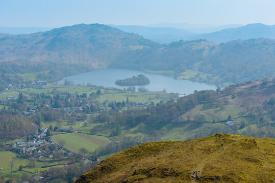 Grasmere village and lake and Loughrigg Fell in the background, seen from the summit of Helm Crag, Grasmere, Lake District National Park, Cumbria, UK.