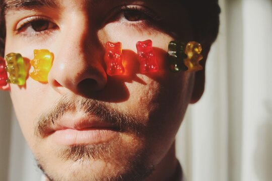 portrait of a young man with colorful gummy bears attached to face