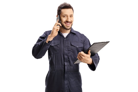 Male worker in a blue uniform talking on a mobile phone and holding a clipboard