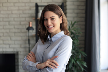 Attractive business woman smiling while standing in the office.