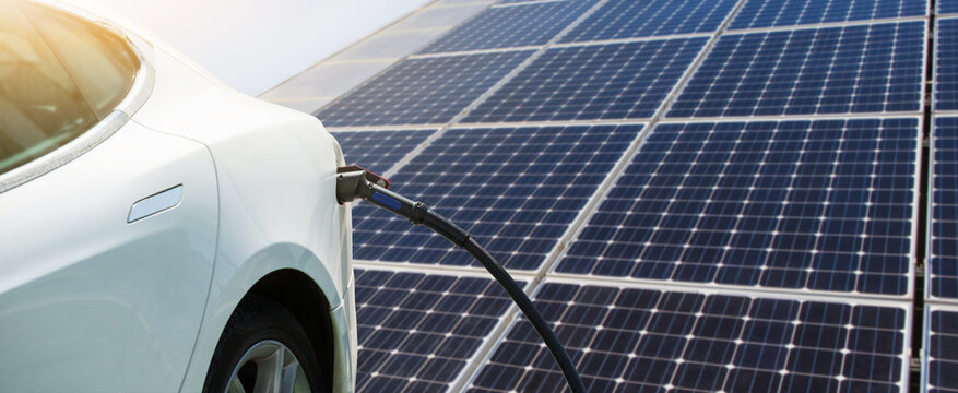 Close up of electric car with a connected charging cable on the background of solar panels