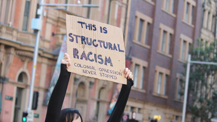 Fototapeta Sydney, NSW / Australia - June 6 2020: Black Lives Matter March. Protesting Aboriginal rights  death of. Sign reading 'This is structural racism, colonial oppression never stopped'.  obraz