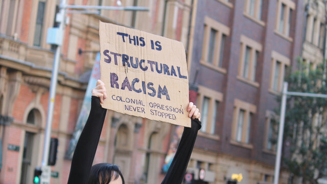 Sydney, NSW / Australia - June 6 2020: Black Lives Matter March. Protesting Aboriginal rights  & death of George Floyd. Sign reading 'This is structural racism, colonial oppression never stopped'.
