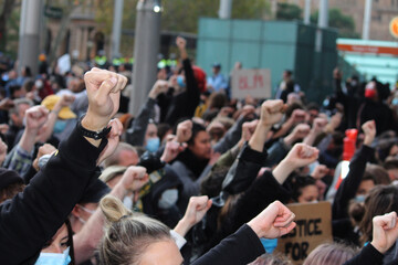 Sydney, NSW / Australia - June 6 2020: Black Lives Matter Protest March. Protesting Aboriginal deaths in custody and the death of George Floyd.  The crowd kneeling with one fist in the air