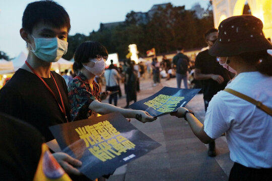 Volunteers hand out posters supporting Hong Kong anti-government movement to people coming to the rally marking the one-year anniversary of the start of the protests in Hong Kong, in Taipei