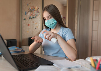 teenager girl, in medical mask, applies an antiseptic spray on her hands, disinfection from bacteria and germs and viruses, laptop monitor, e-education and online lessons, distance learning.