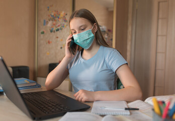 Teenager girl, in a medical mask, disinfection from bacteria and germs and viruses, calls on a smartphone, laptop monitor, e-education and Internet lessons, distance learning.