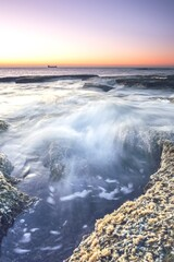 Foto op Plexiglas Purper Beautiful scenery of waterfall in the sea with rock formations at sunset