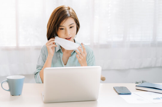 Portrait of young Asian business woman working from home prepare to wear medical disposable mask for protection flu and covid-19.Business woman in quarantine for coronavirus wearing protective mask.