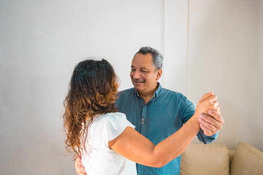 A happy older Hispanic couple having a good time at home. Elderly retirement and the concept of healthy elderly citizens.