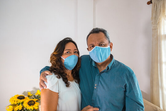 Older couple with medical mask in their living room