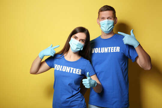 Volunteers in masks and gloves on yellow background. Protective measures during coronavirus quarantine