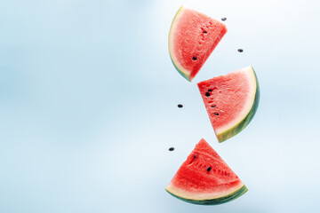 Watermelon slice falling on pastel background. Floating fruits in the air. Flying red fruits....