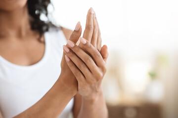 Body Care. Closeup Image Of Black Woman Applying Moisturising Cream On Hands