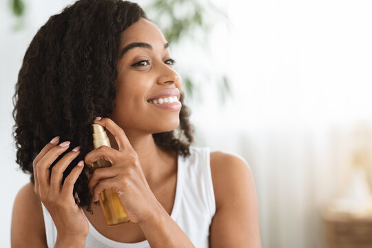 Hair Care. Happy Afro Woman Using Oil For Split Ends At Home