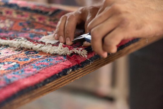 traditional hand sewing fixing with clippers old vintage antique persian carpet up close