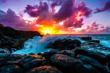 Beautiful scenery of rock formations by the sea at Queens Bath, Kauai, Hawaii at sunset