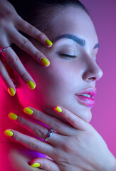 Colorful portrait of beauty sexy model girl. Beautiful woman in bright UV lights. Gorgeous Brunette girl in neon light. Beauty Glamour sensual lady posing. Perfect colourful make-up and nails, Disco.