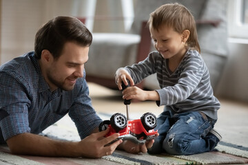 Deurstickers Wanddecoratie met eigen foto Happy father and little son playing with toy car together close up, sitting on warm floor with underfloor heating, cute preschool boy using screwdriver, having fun with dad, enjoying weekend at home