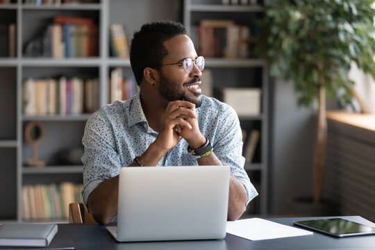 African guy freelancer or office worker take break from work seated at desk in front of laptop looking at window feels satisfied by accomplished work, visualizing relieving fatigue daydreaming concept