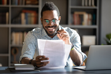 African student guy sitting at desk holding papers printed tasks perform test prepares for entrance...
