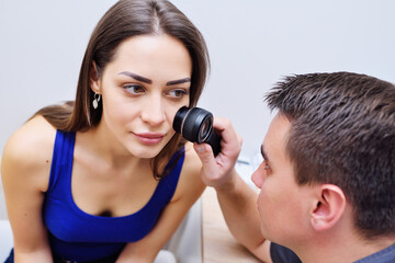Doctor dermatologist examines the skin of the girl's patient for the presence of moles, birthmarks, tumors. Dermatoscopy, prevention of melanoma, skin cancer, Dermatoscope.